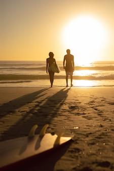 Pareja caminando junto con tabla de surf en la playa