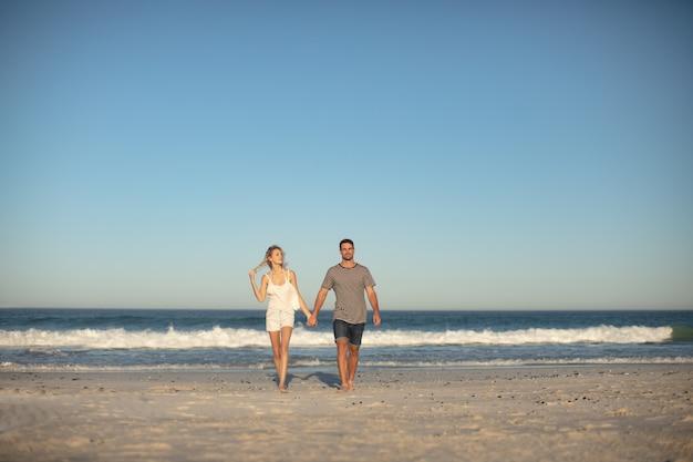 Pareja caminando juntos de la mano en la playa