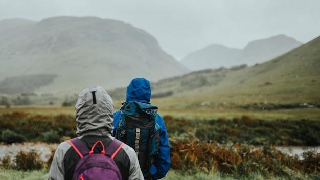 Pareja caminando bajo la lluvia en las tierras altas
