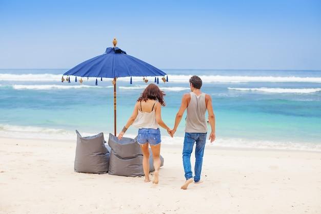 Pareja caminando hacia el mar en una playa de bali.