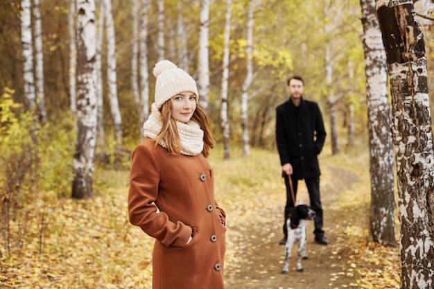 Pareja caminando con perro en el parque y abrazos. paseo de otoño