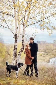 Pareja caminando con perro en el parque y abrazos.