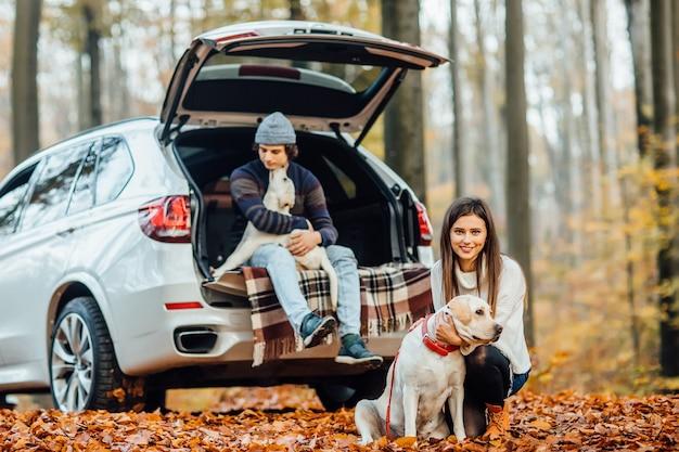 Pareja caminando con perros en el bosque de otoño, propietarios con labrador dorado relajándose cerca del coche.