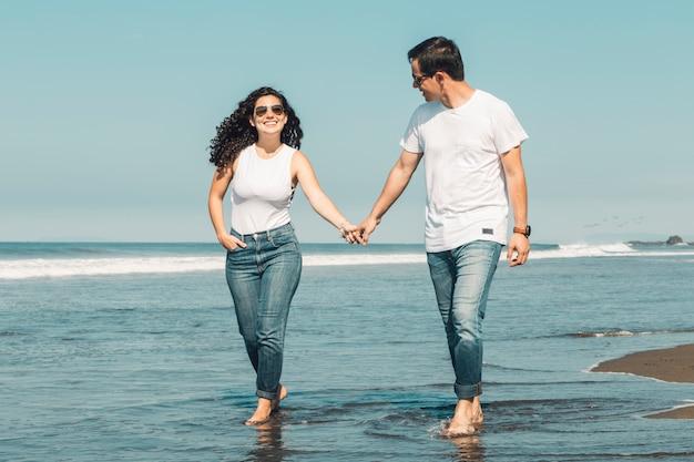 Pareja caminando por la playa descalzo en el agua