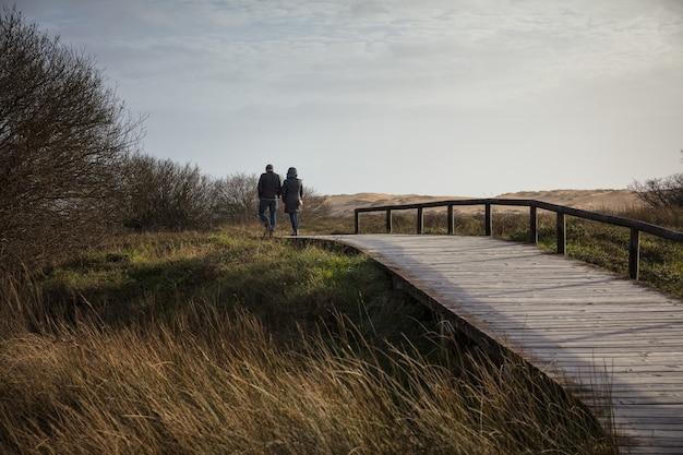 Pareja caminando sobre un puente de madera rodeado por un campo y colinas bajo la luz del sol