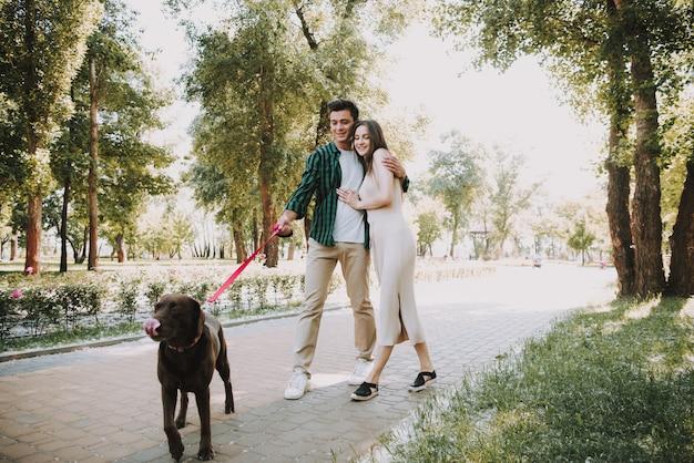 Pareja está caminando con su perro divertido en el parque de verano
