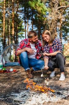 Pareja en camping cocinando marshmellow en llamas