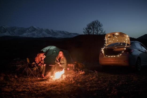 Pareja en camping con fogata en la noche en las montañas