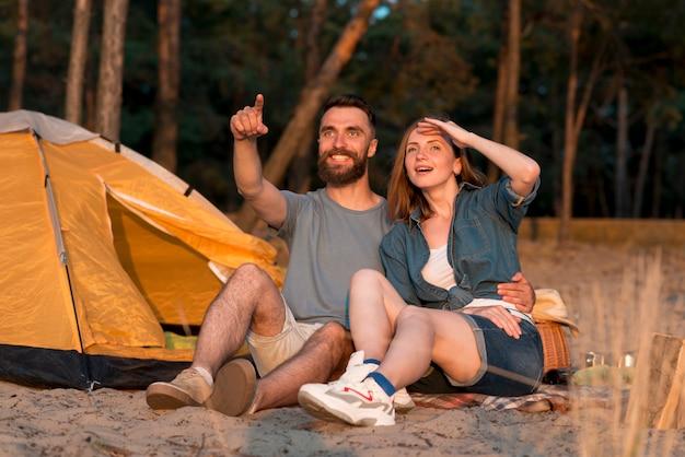 Pareja de camping mirando al cielo