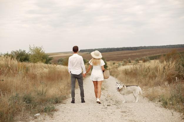 Pareja en un campo de otoño jugando con un perro