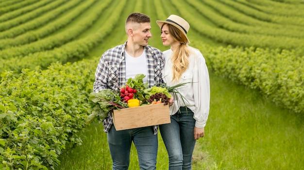 Pareja con canasta de verduras en tierras de cultivo