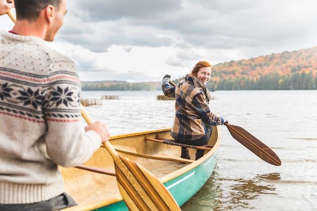 Pareja en una canoa en el lago en otoño, canadá