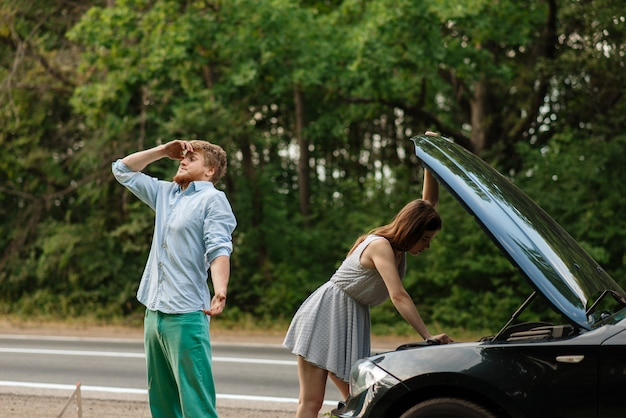 Pareja cansada en el capó abierto en la carretera, avería del coche