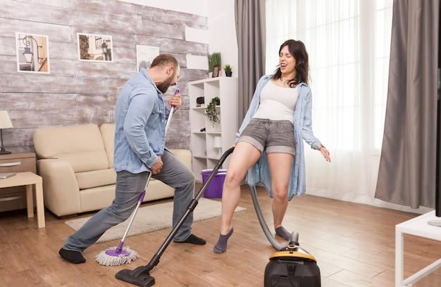 Pareja cantando y bailando mientras limpia la casa