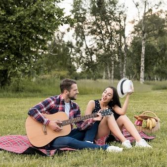 Pareja cantando sobre manta de picnic