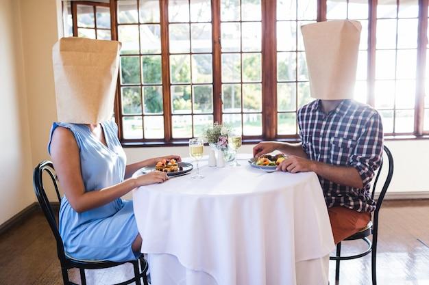 Pareja caras cubiertas con bolsa de papel en restaurante