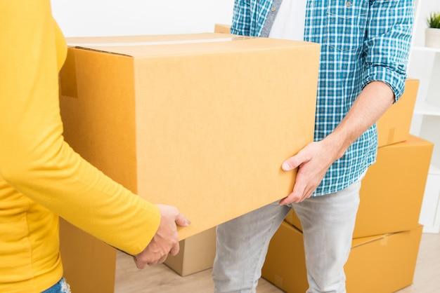 Una pareja cargando una caja se muda a su nueva casa.