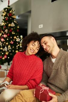 Pareja cariñosa intercambiando regalos de navidad