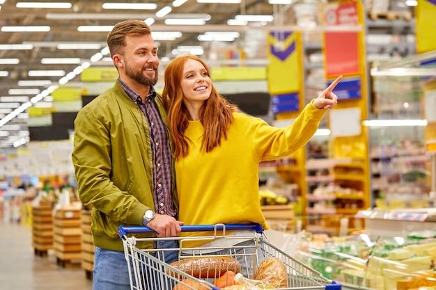 Pareja con carrito de compras comprando comida en la tienda de comestibles o supermercado, la mujer señala con el dedo a un lado, pide al marido que compre algo