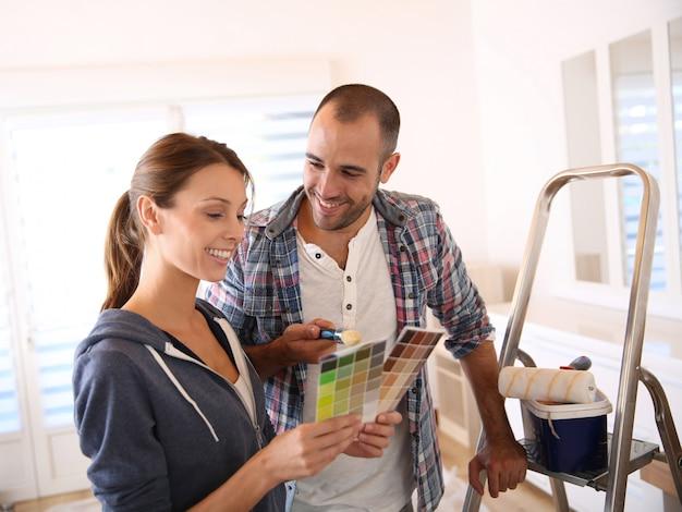 Pareja en casa nueva eligiendo color para paredes