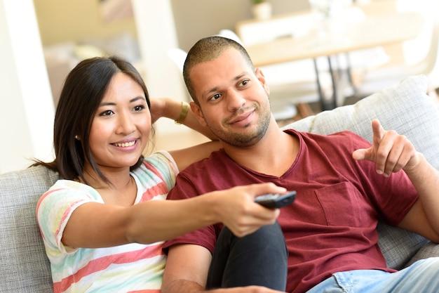 Pareja en casa en el sofá viendo una película en la televisión