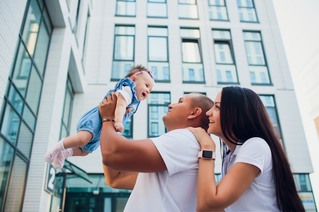 Pareja casada, aman con niño, mujer con hombre sobre sus hombros. contra el edificio de cristal de fondo