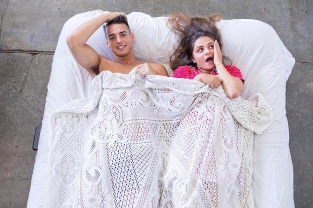 Pareja casada divertida que miente en cama y que oculta debajo de la manta blanca, mirando la cámara con los ojos llenos de alegría.