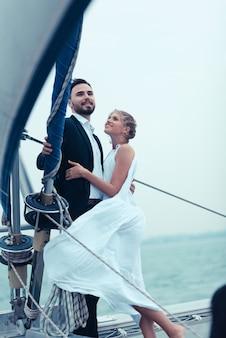 Pareja casada hermosa joven que abraza en el yate en vacaciones
