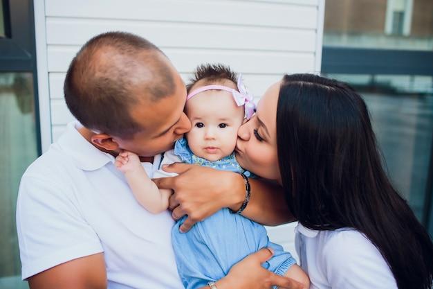 Pareja casada, el hombre está sosteniendo al niño, la mujer está de pie al lado del otro. padres besan niña