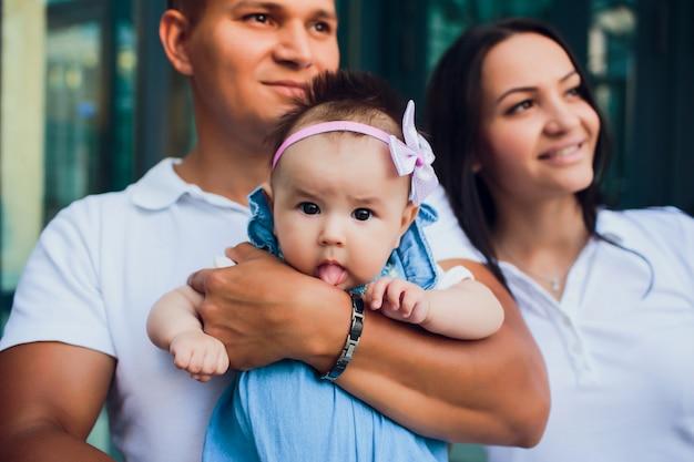 Pareja casada, el hombre está sosteniendo al niño, la mujer está de pie al lado del otro. padres mirando a otro lado. concepto sueño vida futura