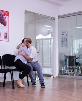 Pareja casada llorando en la sala de espera del hospital escuchando malas noticias del médico abrazándose ...