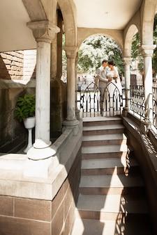 Pareja casada de lujo, novios, posando en el romántico patio de la ciudad vieja