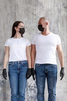 Una pareja casada con máscaras negras y guantes de goma negros.