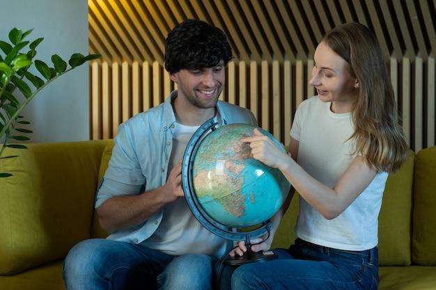 Pareja casada mira el mundo en la sala de estar sentado en el sofá pareja joven eligiendo lugar para viajar