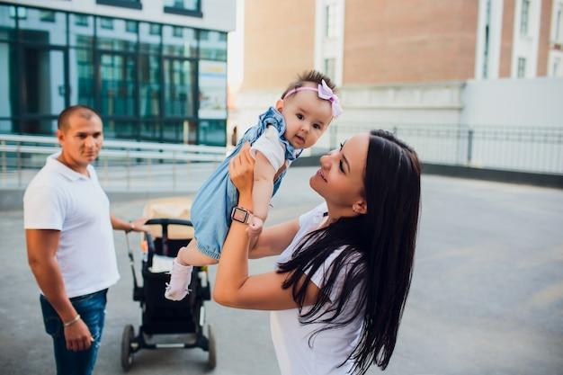 Pareja casada, una mujer sostiene un bebé mientras el padre mira la parte inferior y sostiene un cochecito