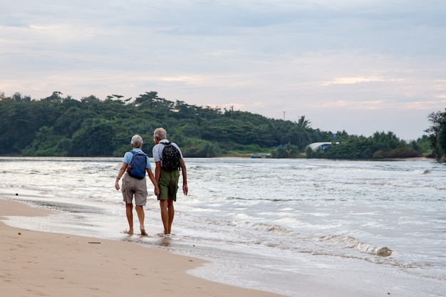 Pareja casada de personas mayores en la playa en la costa del océano