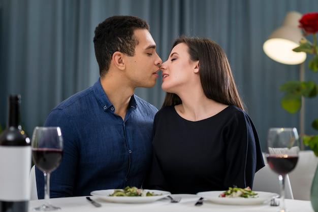 Pareja casi besándose en una cena romántica