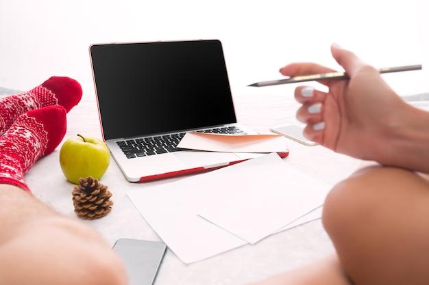 Pareja caucásica en casa usando tecnología de internet. ordenador portátil y teléfono para personas sentadas en el suelo con calcetines de colores.