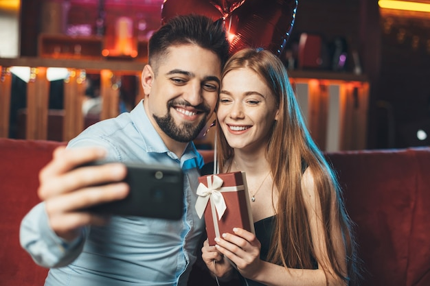 Pareja caucásica celebrando el día de san valentín sostiene globos y hace un selfie usando un teléfono