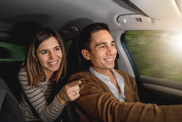 Pareja caucásica dentro del coche sonriendo. la mujer está señalando algo afuera con el dedo mientras el hombre está conduciendo.