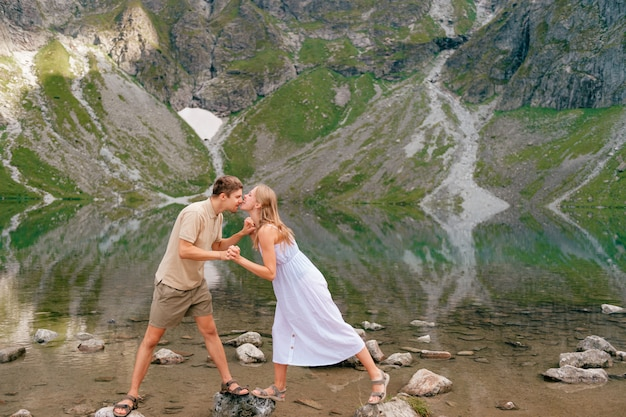 Pareja caucásica divirtiéndose en frente del lago de montaña con reflejos.