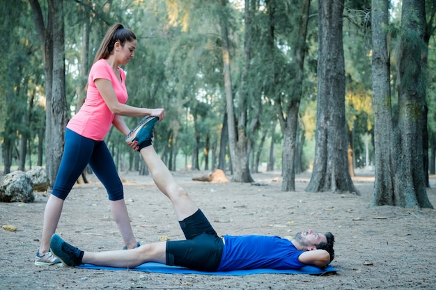Pareja caucásica haciendo ejercicios de estiramiento en un parque