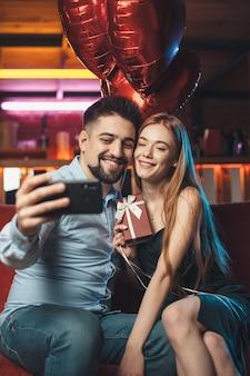 Pareja caucásica está haciendo selfie usando teléfonos y sonríe mientras sostiene globos rojos en el día de san valentín