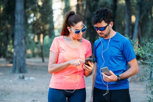 Pareja caucásica viendo la aplicación móvil y haciendo ejercicio en un parque