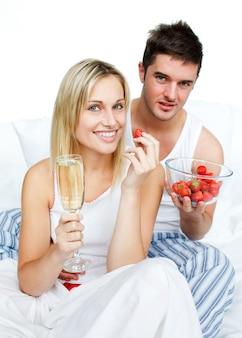 Pareja celebrando un compromiso con fresas y champagne