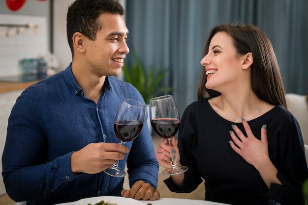 Pareja celebrando el día de san valentín con una copa de vino.