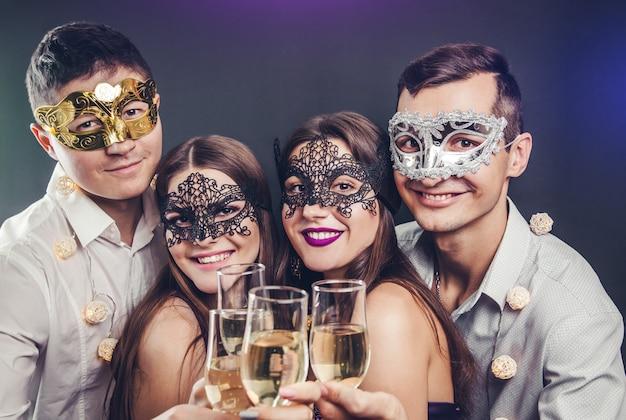 Pareja celebrando la víspera de año nuevo bebiendo champán en la fiesta de disfraces