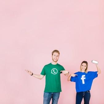 Pareja con celular apuntando a su camiseta con facebook y icono de whatsapp