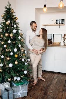 Pareja cerca de árbol de navidad en navidad en casa en la cocina