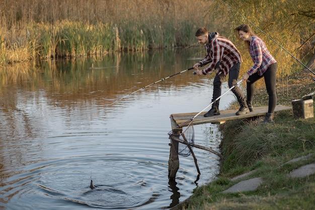 Pareja cerca del río en una mañana de pesca